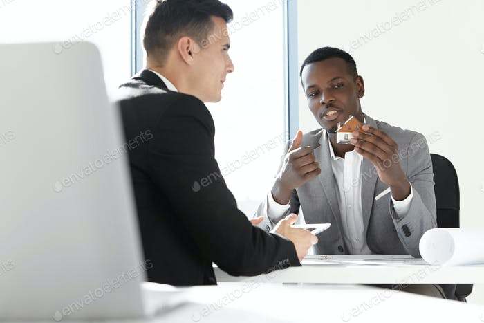 Two business partners having meeting in office: African man in gray suit holding scale model house,