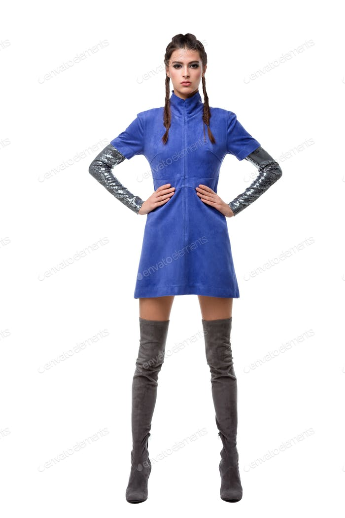 Young beautiful lady standing in blue dress and knee high boots on white background