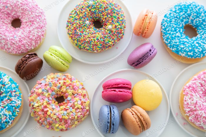 Donuts and macarons on white, close up view