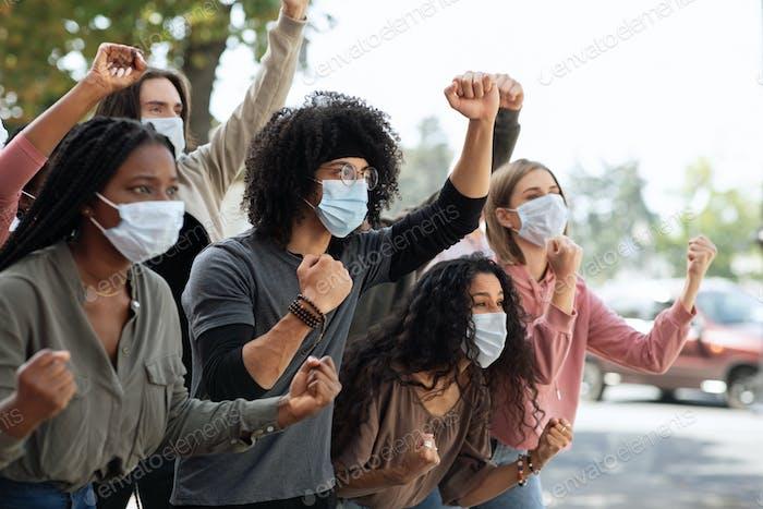 Jóvenes en máscaras protectoras que asisten a la manifestación en la calle