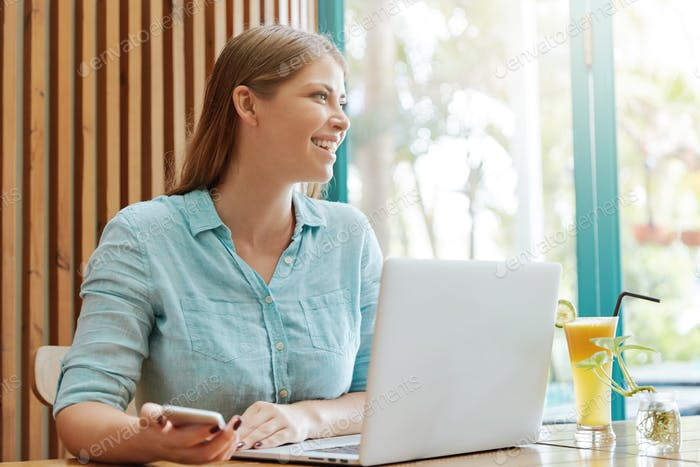 Cheerful attractive female copywriter earns money online, works remotely at laptop computer, holds m