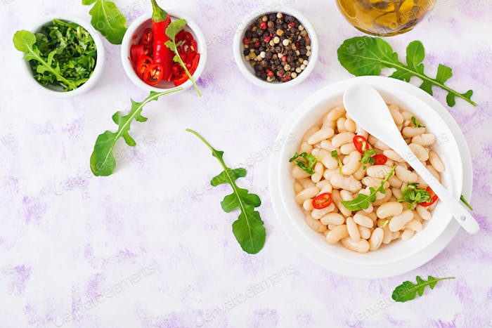 Boiled white beans in a bowl. Diet food. Healthy lifestyle. Sports nutrition. Flat lay. Top iew