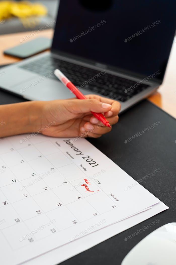 Woman marking January 1, 2021 on a calendar