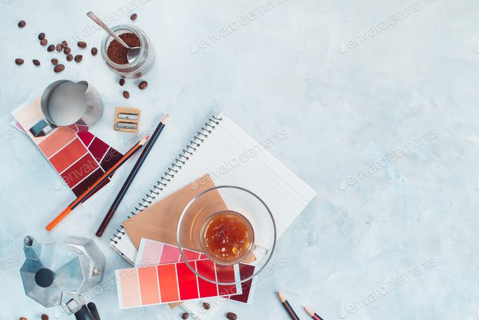 Designer workplace with coffee pot, color swatches, notes and coffee cups. Creative top view hot
