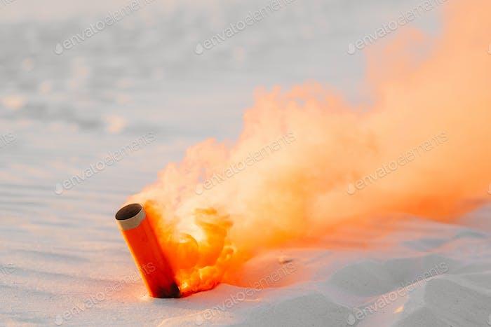 bomba de humo con humo de naranja atrapado en la arena