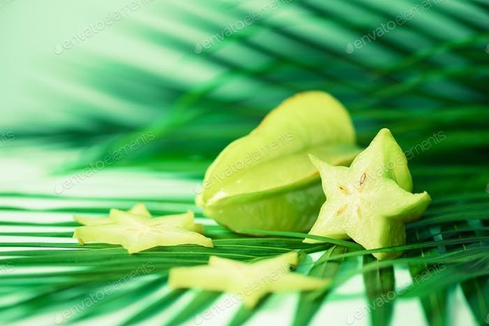 Exotic star fruit or averrhoa carambola over tropical green palm leaves on turquoise background