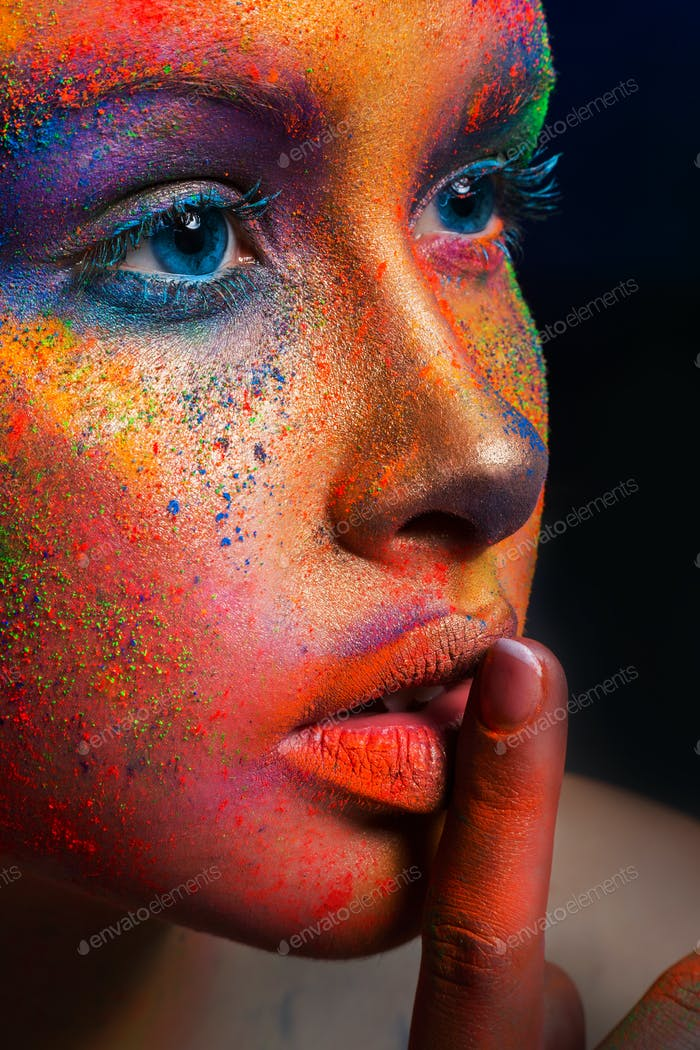 Model with art make-up posing on dark background
