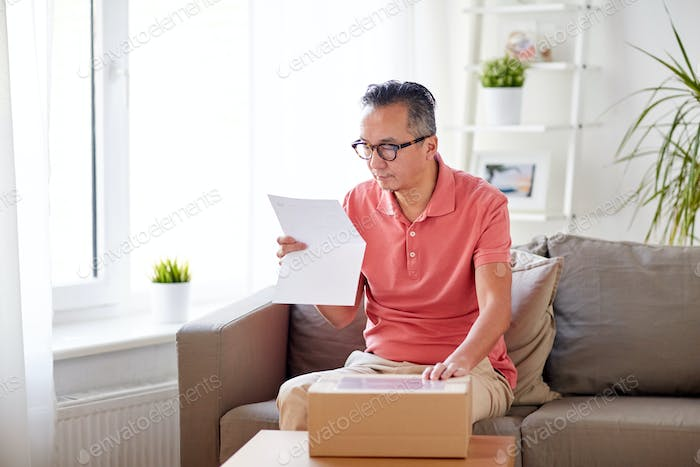 man with parcel box reading invoice at home