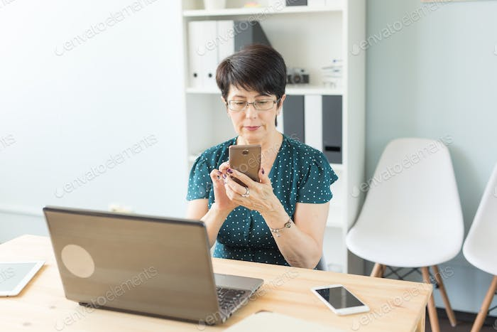 Business, people and technology concept - confident business woman using her smartphone while