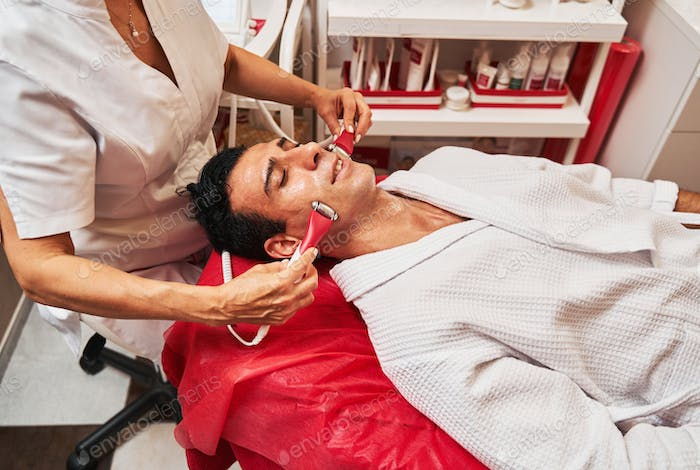 Massage of man face with electric stimulation tools