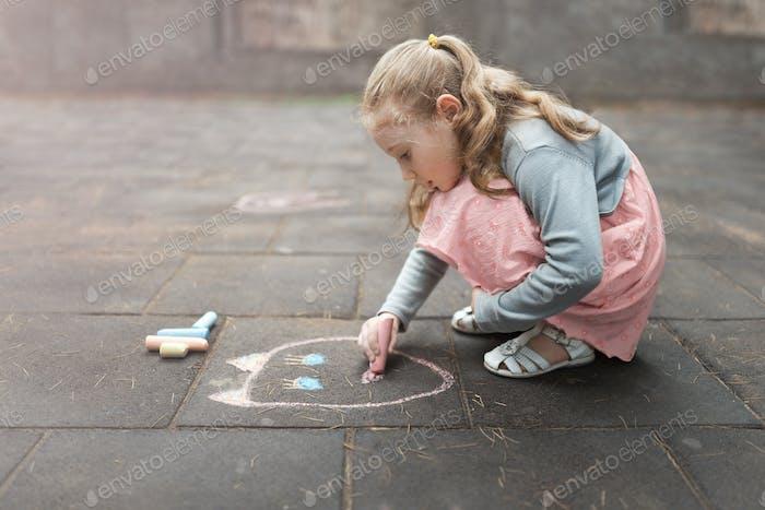 little girl draws chalk on asphalt