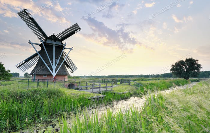 Dutch windmill by river at sunset