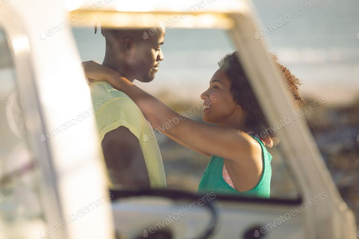 Side view of romantic mixed race couple embracing each other near camper van at beach