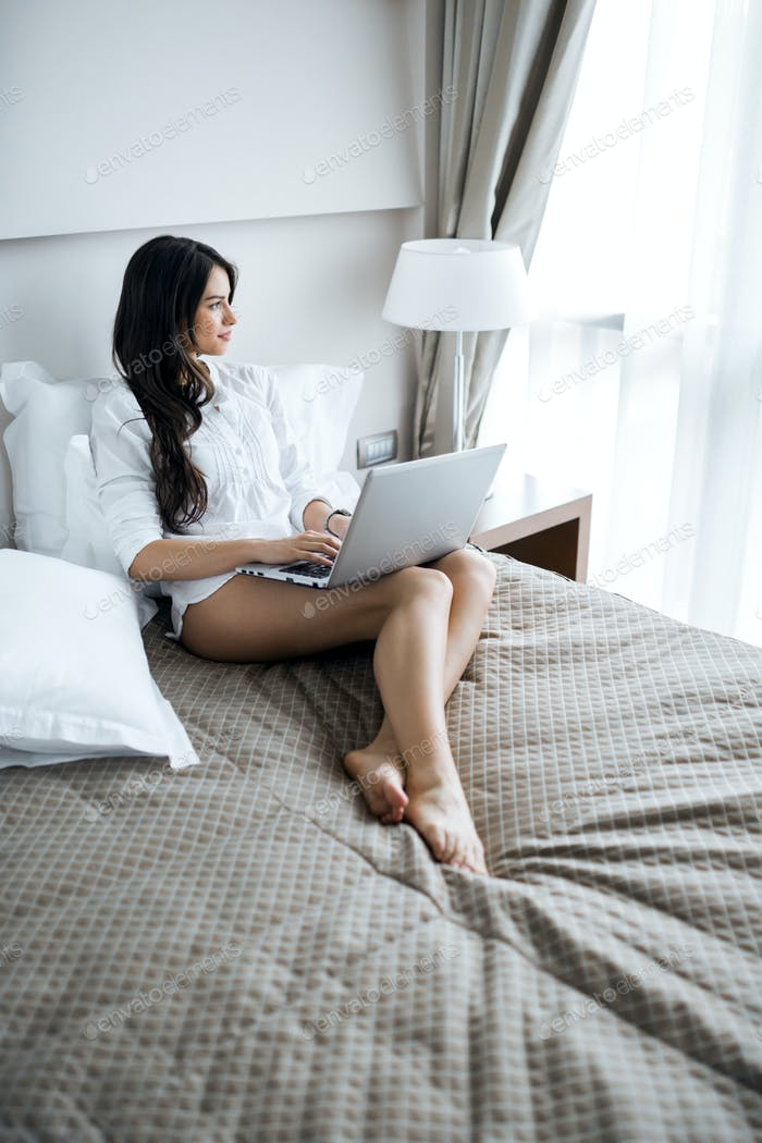 Beautiful woman with sexy long legs in shirt using a notebook in