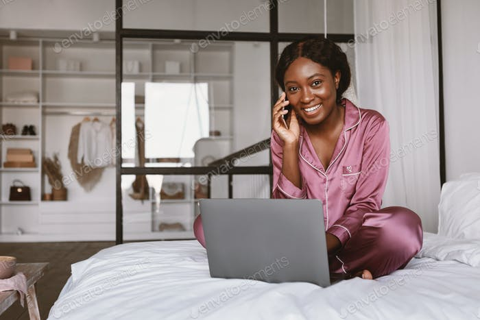 African Lady Talking On Cellphone Sitting At Laptop In Bedroom