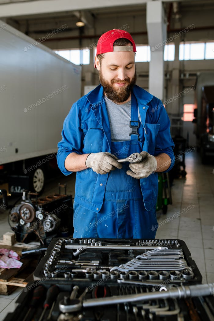 Contemporary young worker of car repair service standing by motor of automobile