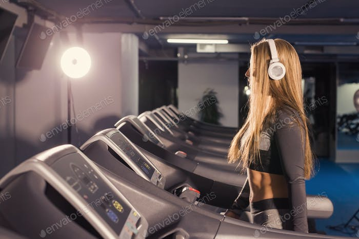 Fitness woman running on treadmill. Girl with muscular legs in gym