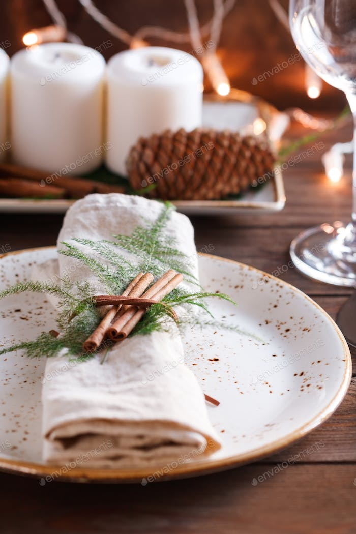 Linen napkin decorated cinnamon sticks and plants on a ceramic plate