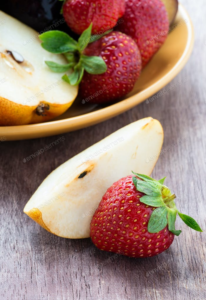 Fresh pear and strawberry on a wooden background