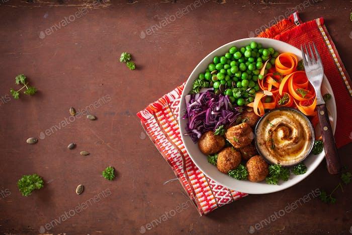 healthy vegan lunch bowl with falafel hummus carrot ribbons cabb