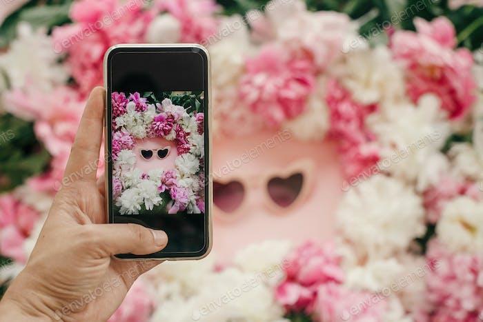 Hand holding phone and taking photo of stylish girly flat lay