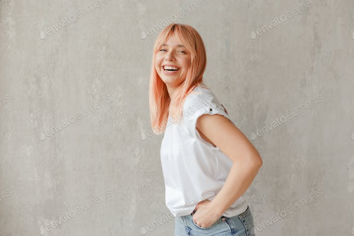 Young joyful woman in white t-shirt with dyed hair laughing