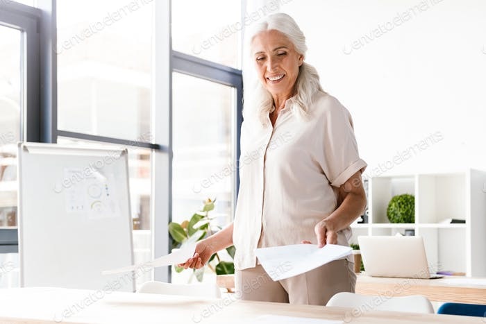 Happy mature business woman analyzing documents