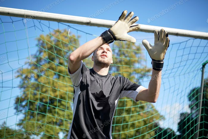 goalkeeper or soccer player at football goal