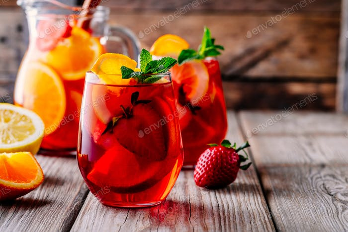 Homemade red wine sangria with orange, apple, strawberry and ice in glass and pitcher