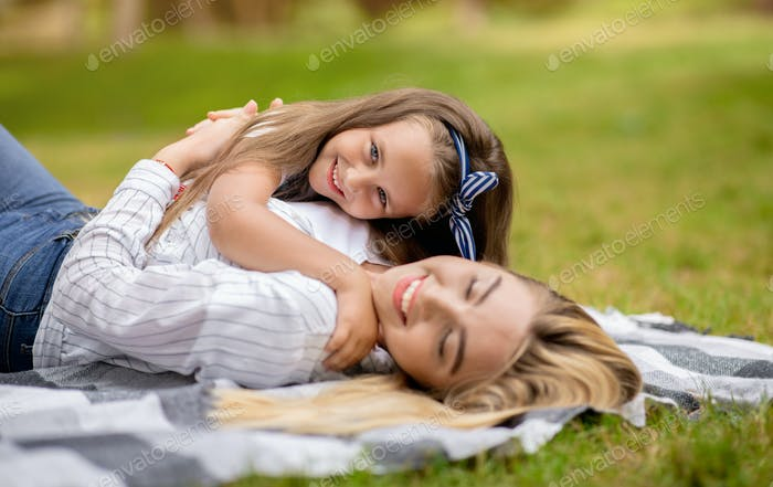 Happy Mom Embracing Little Daughter Lying On Blanket In Park