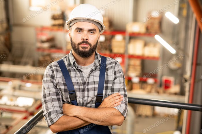 Young confident contractor or engineering staff looking at you in warehouse