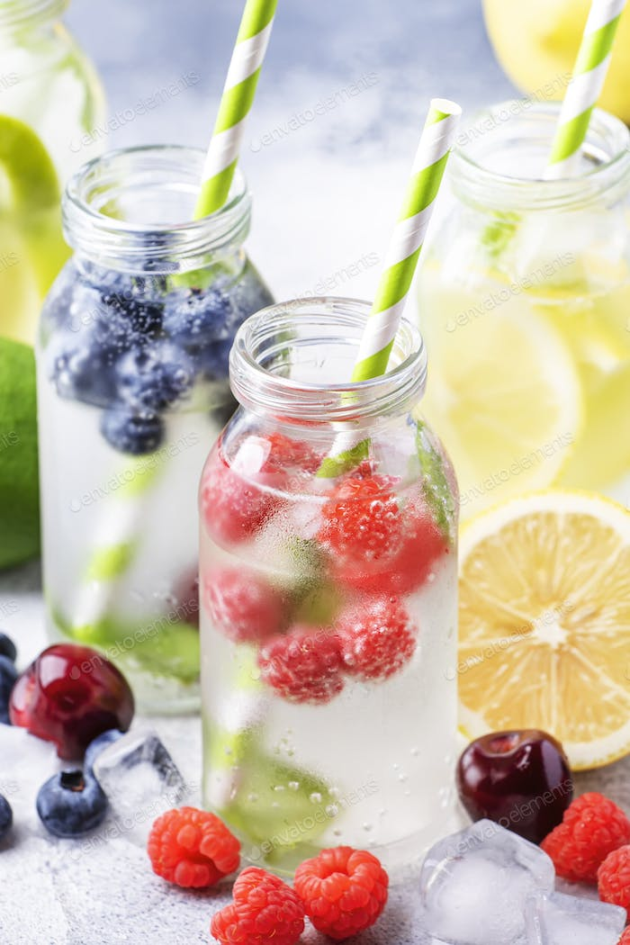 Berry and citrus fruit infused summer cold drinks in glass bottles
