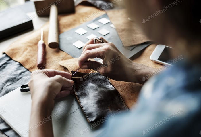 Closeup of craftsman sewing leather handicraft