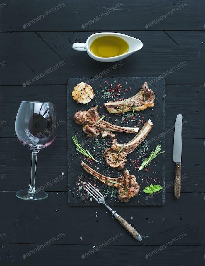 Gegrillte Lammkoteletts. Lammregal mit Knoblauch, Rosmarin, Gewürzen auf Schiefertablett