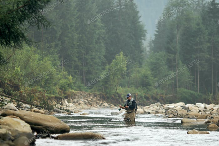 Mann steht mit fliegender Rute im Wasser und angeln