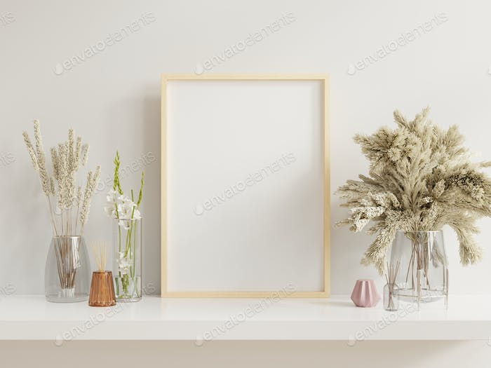 Wooden frame leaning on white shelf in bright interior.