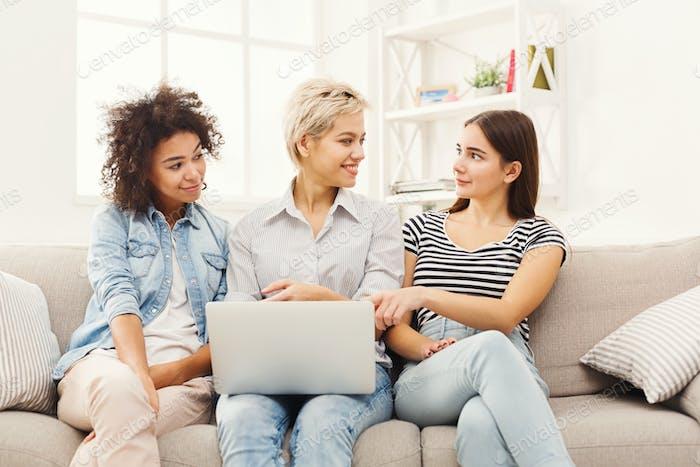 Three beautiful women using laptop at home
