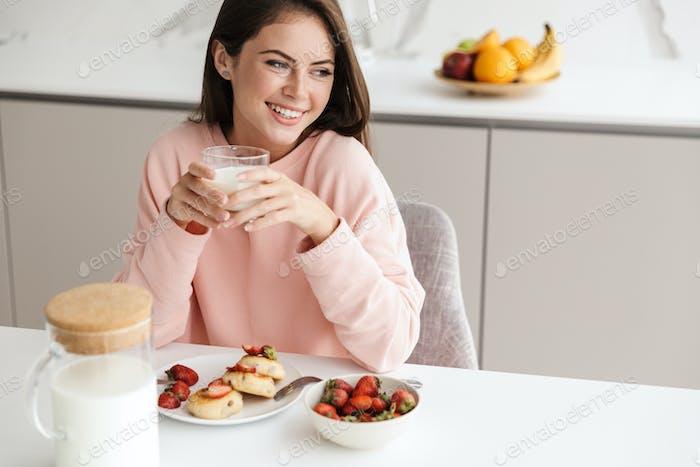 Beautiful smiling young girl having tasty healthy breakfast