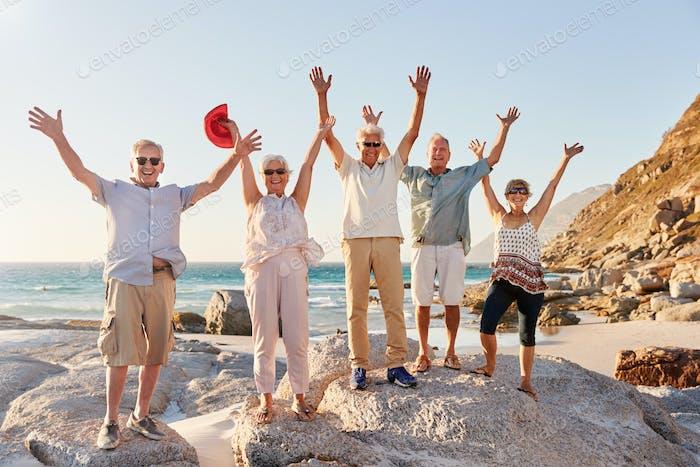 Vertical de mayores Amigos de pie en rocas por Mar en verano Grupo de vacaciones con brazos extendidos