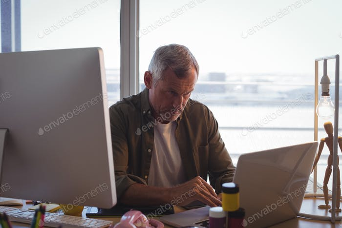 Serious businessman working on laptop at office desk