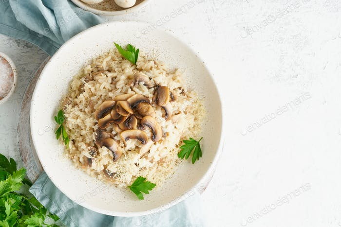 Risotto with mushrooms in plate. Rice porridge with mushrooms and parsley