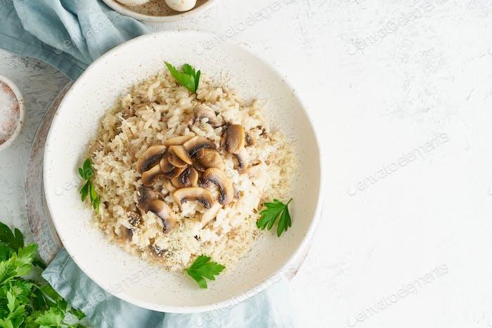 Risotto mit Pilzen in Platte. Reisbrei mit Pilzen und Petersilie