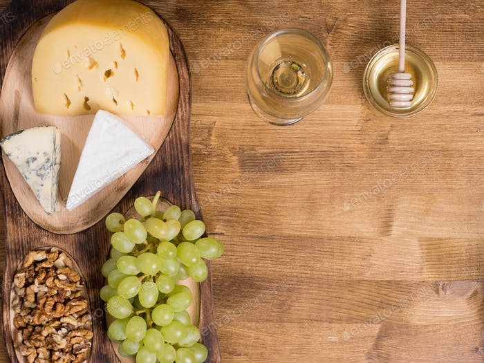 Grapes, white wine. honey and nuts over rustic wooden table