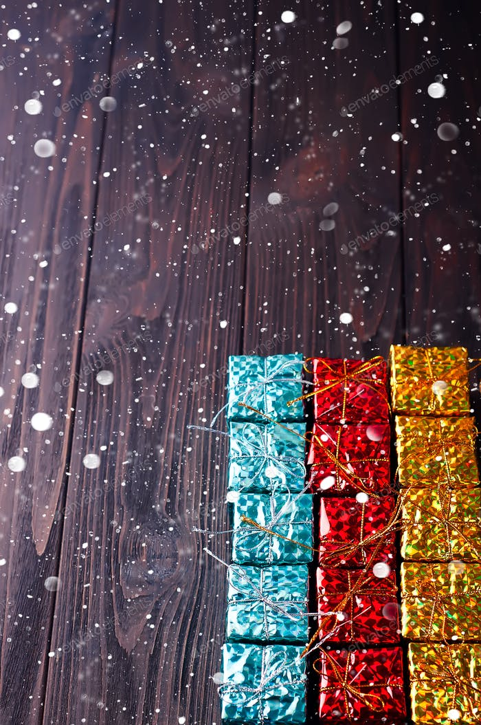 Christmas gift boxes on wooden table with snow.
