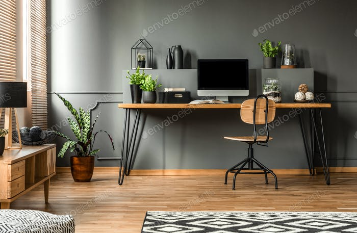 real photo of a dark interior with wooden desk chair and comput