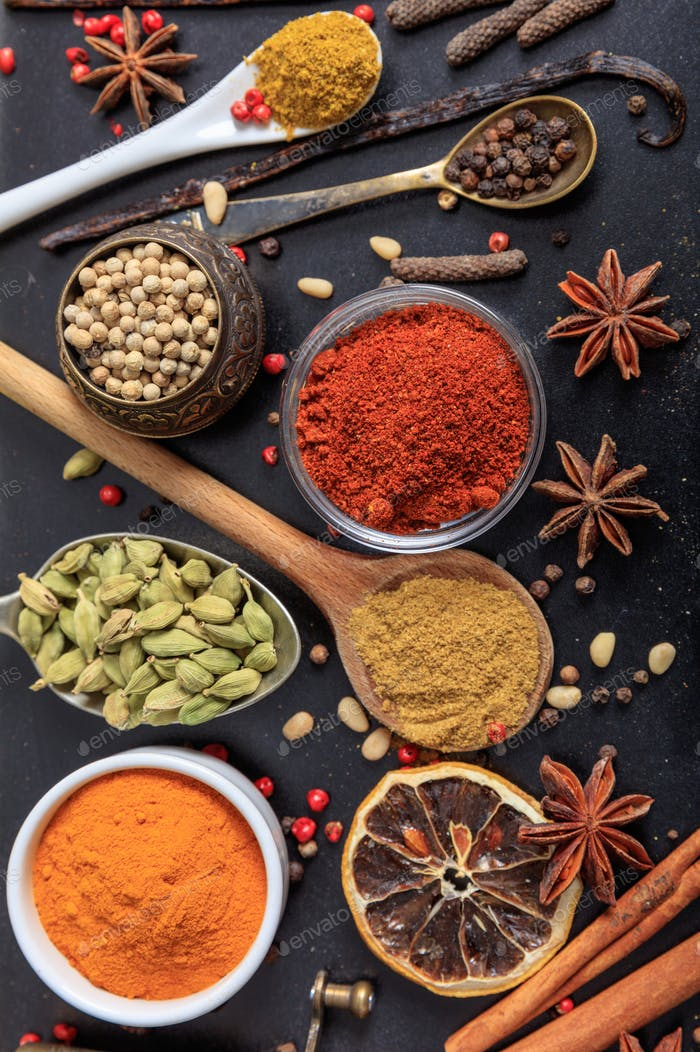 Spices and herbs flat lay, black color background, top view.