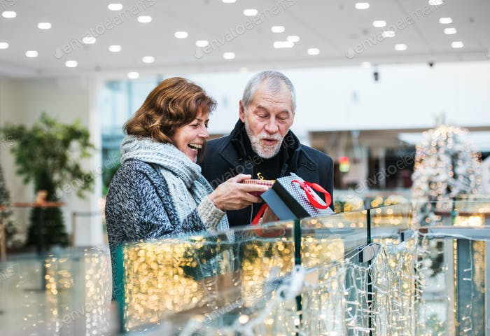 A senior woman giving a present to a man in shopping center at Christmas time.
