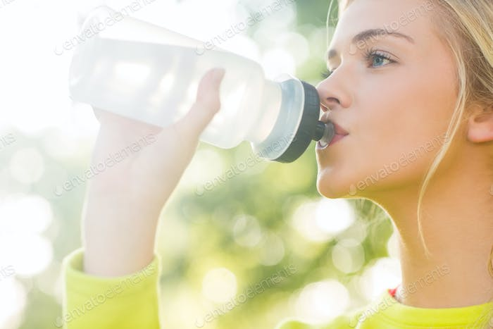 Fit blonde drinking from sports bottle in a park on a sunny day
