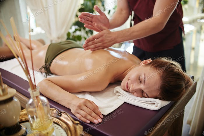 Smiling Woman Enjoying Massage in SPA