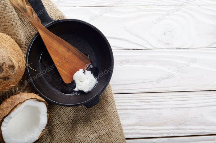 Coconut, shell with meat, cast iron skillet and spatula on hemp
